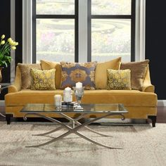 This gold sofa with patterned back cushions and accent pillows is a strong nod to Hollywood Regency style. The soft premium upholstery, deep seats and multi-cushioned back ensures a comfortable lounging experience. The solid wood frame also ensures durability. A nailhead trim completes the look.