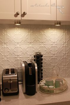 Pressed tin splashback/backsplash with downlights installed in the bottom of the wall cupboards, lighting up the little coffee/toast making area