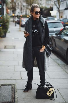 black sweatshirt + black joggers + gray sleeveless cardigan + dark gray blanket scarf + black wedge sneakers + black purse