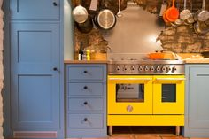 Sustainable Kitchens - A Playful Shaker Kitchen . The bold contrast of colours with the France-shaped stainless steel splashback is very contemporary. The Bertazzoni range cooker is painted Ferrari yellow creating a focal point for the kitchen. The shaker style cabinets painted in Stone Blue (Farrow & Ball) add a nice contrast.