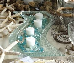 Top Coastal Candle Centerpieces for a Warm & Festive Table..wavy bubble glass..looks like a steam of water with pebbles.