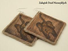 """Kolczyki z kolekcji """"Rootz"""" - romby o przekątnej/ średnicy 7 cm, z drewnianej sklejki, ręcznie malowane farbą akrylową z obu stron, w odcieniach brązu, z motywem słonia, zabezpieczone lakierem, zdobione sznurkiem jutowym, na otwartych biglach. Dzieło Wielkiego Słonia w Czerwone Paski."""