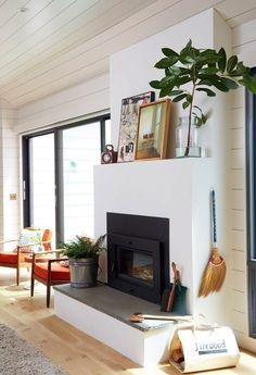 Minimalist modern fireplace styled with art and branches.