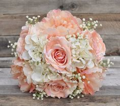 Silk wedding bouquet made with peach roses, peonies, ivory hydrangea and babies breath.