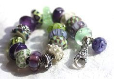 Trollbeads creation with purples and greens.  Very appealing. www.trollbeadsgal...