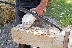 man snijd een klomp uit een stuk hout