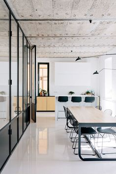 Minimalist dining space with a light wood dining table and black wire chairs