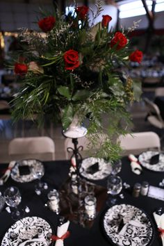 Wedding centerpiece with red roses in a cream urn lifted on a tall metal candlestick