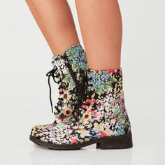 Get lost in a daze of daisies, sunflowers, violets, tulips and daffodils when you‰Ûªre stomping through the concrete jungle of city smog. Wrap your rough edges in bright spring florals with these Doc Marten inspired boots. In a matted black fabric, these printed boots are exploding at the seams with sweet flowers you can practically smell. These high top boots come with a stacked heel, black laces and an inner zipper. Rock these dreamy boots with a jersey maxi in bold colors for your daily…