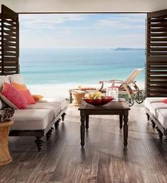 Stylish beach living room with dark wood furniture and floors.