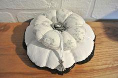 """Pique-aiguille composé de deux """"citrouilles"""", l'une en drap ancien bordé de dentelle noire cousue main, la seconde en tissus fond blanc orné de petites roses et d'écritures. Le - 11119379"""