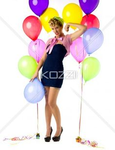 pin up birthday - Woman posing with one arm up beside 2 groupings of helium filled balloons. Model: Carrie Galbraith