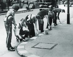 18th September 1939 Women in a civil defence unit paint white squares along the kerb to facilitate night-time driving in London. Photo by Evening Standard