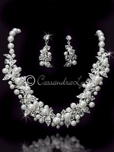 Rhinestone dotted leaves and ivory pearls create a wonderful design in this bridal jewelry set. The pearls are a light ivory that would match almost any color ivory dress. The necklace is 16 inches lo