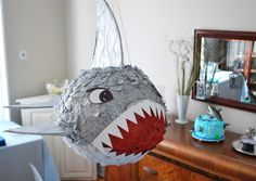 Ask Holly: Making A Shark Piñata - Here is what you will need: A balloon Newspaper torn into long strips Liquid starch White glue Grey, white and red tissue paper Foam core or poster board White card-stock or poster board Strong string or twine Scissors and or and utility knife for cutting foam core Candy