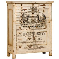 """Hand-painted vineyard art work over a creamy off-white, distressed finish. The artwork features a painting of a French chateau and the words """"Chateau Pomys - Cru Bourseois, Sainte Estephe""""."""