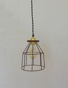 This simple industrial wire cage pendant cone ceiling light is stripped back to its barest form. The handcrafted metal has a distressed rust finish.