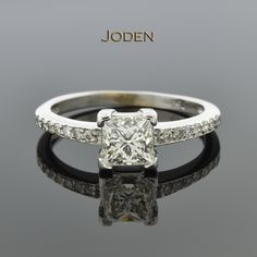 A simple engagement ring centered around a 1.00 carat princess cut diamond. This diamond has a color grade of J-K and a clarity grade of VVS(1-2). A clean row of 14 round brilliant cut diamonds have a weight of .14 carat total weight. These diamonds have an average color grade of H-I and an average clarity grade of SI(1-2).
