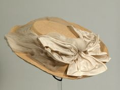 1865 hat, cream silk, drawn up at center; silk head lining beneath. Brim faced with cream georgette tucked in wavy lines. Straw moulded into shape. The edges of an originally round brim folded under. Edge wired. Trimmed with a wide band of loosely pleated georgette held out by wires, the tail going beyond the brim. Large cream silk bow at front held in place by a past brooch. Fastened with narrow black elasticated tape loop. Snowshill Manor © National Trust / Richard Blakey