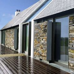 Paris studio Opus 5 Architects completed this island house in Brittany, France, featuring a glazed façade with sections covered by stone screens.