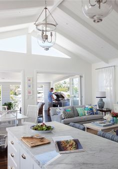VJ raked ceiling, exposed beams, window over the bifolds, white curtains, rear patio, grey and white furniture with pops of colour