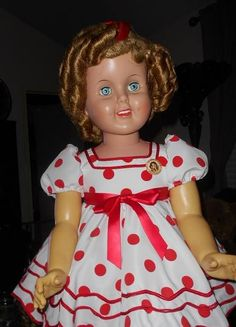 "36"" ""Curly Dimples"" doll, a wonderful Shirley Temple look-a-like doll, made by Earle Pulliam of Canada. Her rooted hair, it nice and thick, and has been re-styled into lovely curls. She will come wearing the red and white coin dot, dancing dress from Shirley's movie ""Stand Up and Cheer."" She is a heavy vinyl doll, has flanged head and limbs, and is a non walker. She has white buckle up, Mary Jane shoes with lacy socks, and undies. A pert red hair ribbon, and a reproduction Shirley Temple…"