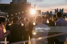 String lights over crowd at rooftop party