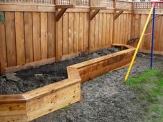 Raised planter box along fence that doubles as a bench. Also brackets for hanging plants.