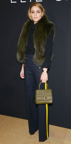Olivia Palermo selected a black cowl-neck knit half-tucked into a pair of nautical-inspired wide-leg pants with a bright yellow streak along the leg. An olive fur stole and a matching mini top-handle purse completed her look.