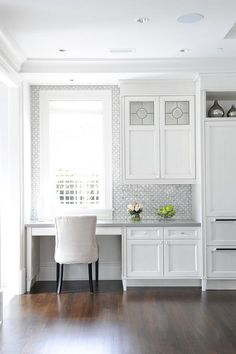 An ivory linen chair sits at a white built-in desk fixed in a kitchen and boasting a gray quartz top mounted beneath a window farmed by white and gray mosaic glass and porcelain tiles.