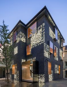 The studio Atelier Archmixing in China has a mixture of gray and luminous bricks that appear the same in the day light and distinctly different in the evening.