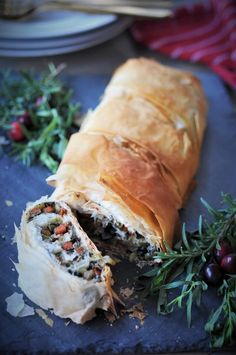 Sliced Vegan Vegetable Wellington on a gray piece of slate with fresh sprigs of tarragon, rosemary, and a few fresh cranberries for decoration.