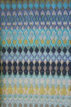 Alpenglow Fabric A woven fabric with multicoloured embroidered bands of turquoise, green, black and blue.