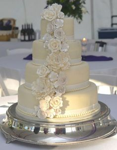 4 tier round wedding cake, covered in white chocolate fondant and adorned with a cascade of gumpaste flowers,