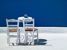 Santorini… Two simple white chairs facing the deep blue Mediterranean sea. The essence of Greece