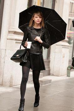 Look de Taylor Swift: Chaqueta de Cuero Negra, Vestido Skater Negro, Botines de Cuero Negros, Bolso de Hombre de Cuero Negro