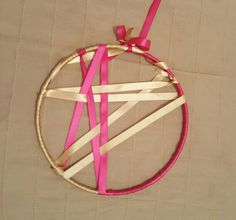 Wreath made by embroidery hoop and satin bands. I had left with a piece of an embroidery hoop(I used the previous one to make a dreamcatcher for my sister) so I decided to turn it into a wreath. I dressed it with satin bands in light gold/beige and fuschia, put a bow and large band for hanging and voila! Still seeks for a place to be hanged in our new apartment though...