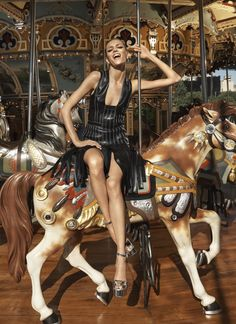 Sitting on a carousel, Anja Rubik is all smiles in leather fringed dress for fall 2016 Lookbook