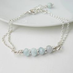 A delicate sterling silver bracelet with small shimmering aquamarine gemstones.Four beautiful little beads of the semi-precious gemstone, aquamarine, sit at the centre of this double chain bracelet. The aquamarine has an attractive faceted cut which helps to catch the light. Little sterling silver beads compliment each bead. A round bead of aquamarine hangs by the clasp adding a pretty detail. Aquamarine is the birthstone for March. Arrives in a white gloss gift box with foam…
