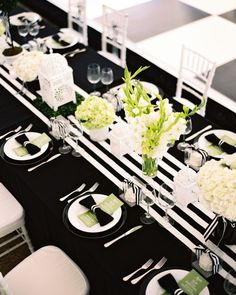 Long tables were covered with black linens and striped runners. Brocade Designs created simple arrangements of hydrangeas, gladiolas, roses, and peonies that were combined candlelit lanterns.