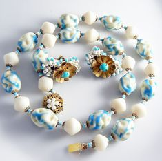 Smooth cream glass beads alternate with rippled indented turquoise and cream oval art glass beads. In between each bead are glass spacer beads of cream and turquoise color and antiqued gilt filigree b