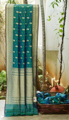 THE GREEN AND BLUE SHOT BROCADE BENARES SILK IS ENHANCED BY THE GREENISH BLUE WITH GOLD MOTIFS BORDER AND PALLU THAT ADDS BEAUTY TO THE SAREE.