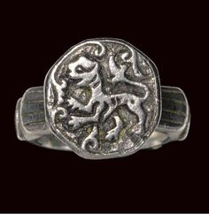 This is a silver ring with a silver bezel featuring a lion. The lion was symbolic of the Seljuk power. The lion is in profile, rearing up, surrounded by curliques. The bezel has a 1.9cm diametre and the ring itself 8.5cm