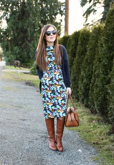 Floral midi dress, navy cardigan, camel boots.