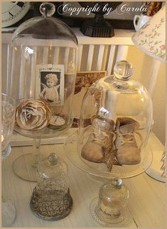 Vintage decor under cloches - I love the baby shoes!