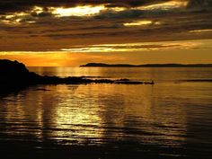 Sunset over Uisead Point, Machrihanish, Nr Campbeltown, Kintyre, Argyll, Scotland. Islay in the background