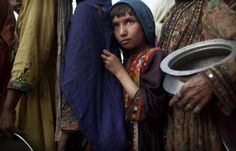 Pakistanis line up at a food distribution point for families displaced by flooding at a temporary camp, in Sukkar, Sindh province, southern Pakistan, Thursday, Aug. 26, 2010. (AP Photo/Kevin Frayer)