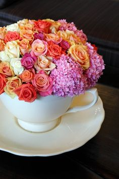 Buy some teacup planters at a  garden store and fill it with bicolored red and white mini roses. Painting the roses red! (Pictured - A handtied posy of roses and hydrangeas served up in a  teacup.)