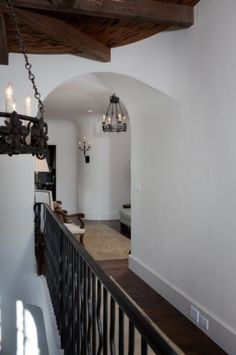 Iron fixtures in keeping with stair railing mediterranean hall by Thomas Thaddeus Truett Architect