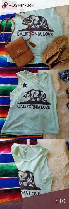 California Love Cut out tank Pale Turquoise Tank has cut off Sleeves and a cut out peep hole back with small tie knot. Print is California flag bear w California Love Text in fades black. Material is very light. Color is light,  pale turquoise. Good condition except for light markings on bottom and back highlighted in last pic. Size is S-M depending on desired fit, loose or tight Audrey 3+1 Tops Muscle Tees
